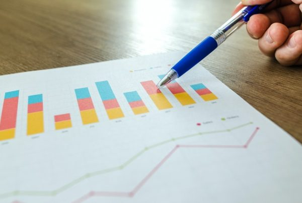 A person pointing to a web analytics graph with a pen