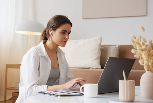 Thoughtful woman with AirPods in using a laptop on a coffee table in their living room. A notepad, vase and cup are next to her as she works on link building for SEO