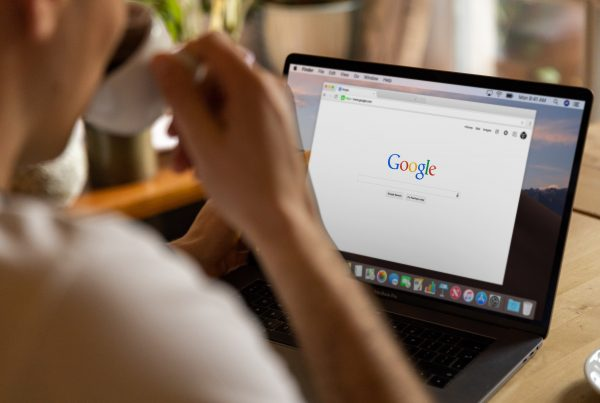 Person sat at a desk drinking coffee, looking at a laptop screen with a tab for Google open, researching how to improve SEO